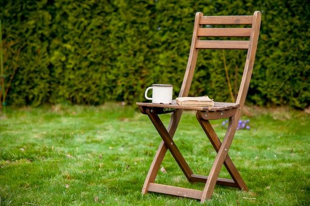 Livro antigo com uma xícara de chá sobre uma mesa na grama verde na primavera