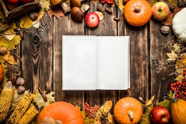 Livro antigo de comida de outono com frutas e vegetais de outono em fundo de madeira