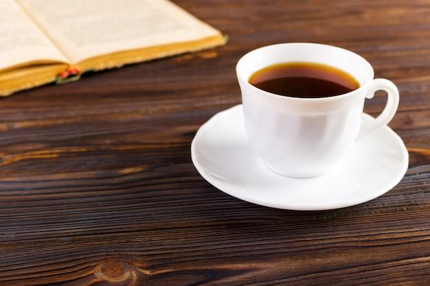 Livro antigo e uma xícara de café em um fundo de madeira, imagem enfraquecida