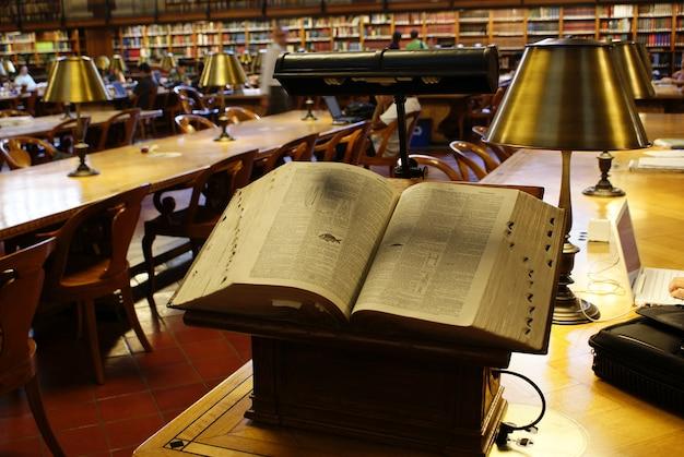 Livro antigo, tratado de biologia, aberto em um púlpito em uma biblioteca pública