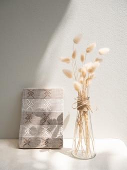 Livro artesanal e composição de flores secas de lagurus ovatus em um moderno vaso de vidro na mesa bege e parede de cimento