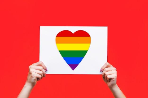 Livro branco com bandeira lgbt em forma de coração em mãos femininas isoladas sobre fundo vermelho