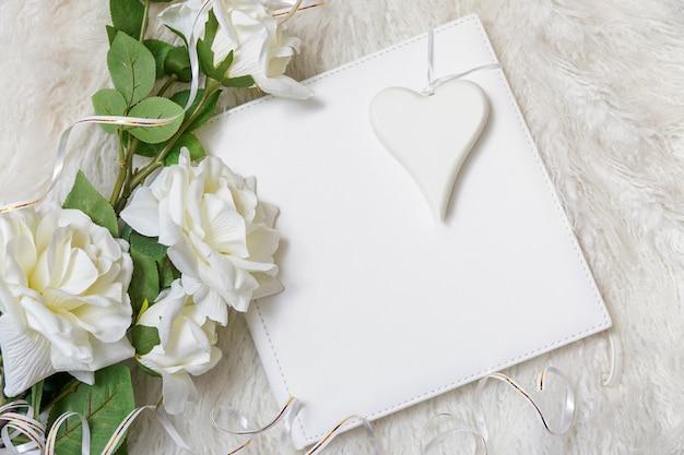 Livro branco com buquê de rosas e coração branco fundo