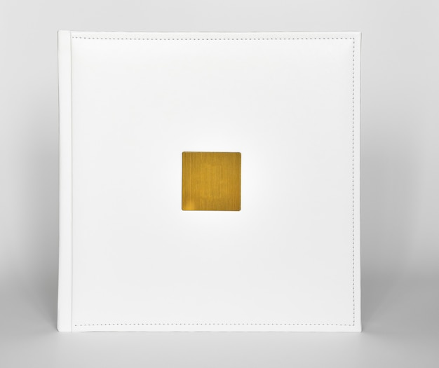 Livro branco com capa de couro com uma inserção de metal dourado para inscrição