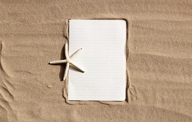 Livro branco com estrela do mar na areia.