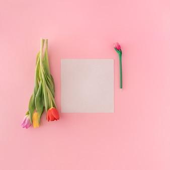 Livro branco com três tulipas vibrantes em fundo pastel. espaço de cópia plana leigos dos namorados.