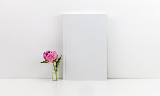Livro branco com uma peônia rosa