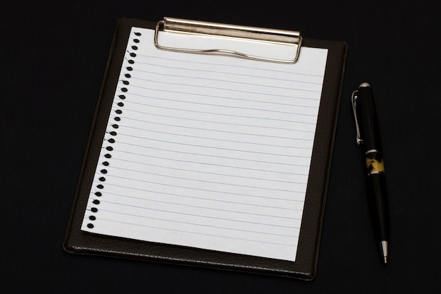 Livro branco e caneta na mesa preta