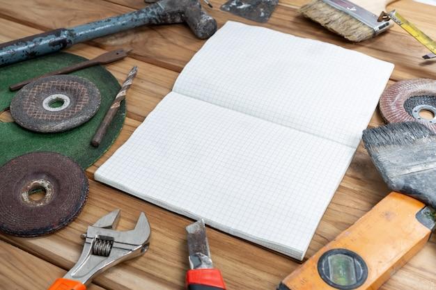 Livro branco e conjunto de ferramentas manual no assoalho de madeira.