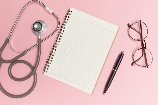 Livro branco em branco do caderno com caneta de tinta preta, estetoscópio, caneta e bloco de receitas em branco. remédio ou farmácia. formulário médico vazio pronto para ser usado. tecnologia da informação médica moderna.