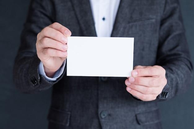 Livro branco em branco nas mãos do homem. conceito de cartão de visita. espaço vazio para o texto.