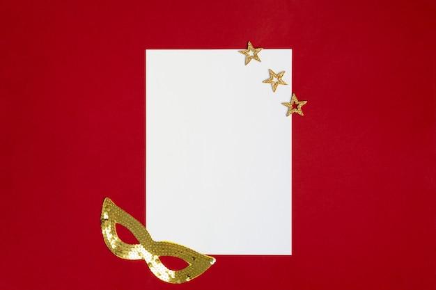 Livro branco em vermelho com máscara dourada festiva de carnaval e estrelas de natal