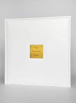 Livro branco encadernado em couro com encarte em metal dourado com inscrição em latim - em período não reembolsável. produtos de impressão. photobooks e álbuns. produtos individuais.