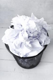 Livro branco na lata de lixo