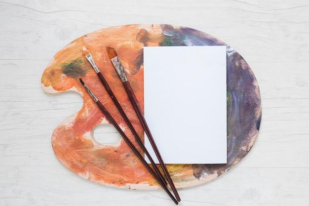 Livro branco na paleta com pincéis