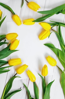 Livro branco para o seu texto e buquê de tulipas amarelas sobre fundo de madeira. conceito de férias.