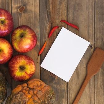 Livro branco perto de frutas e legumes