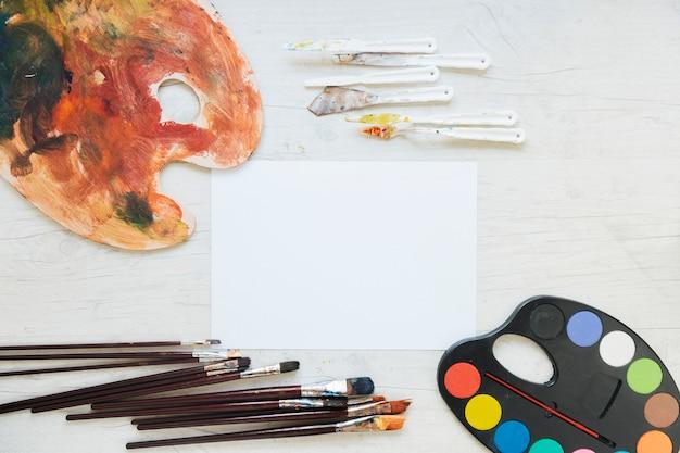 Livro branco perto de paletas, facas e pincéis