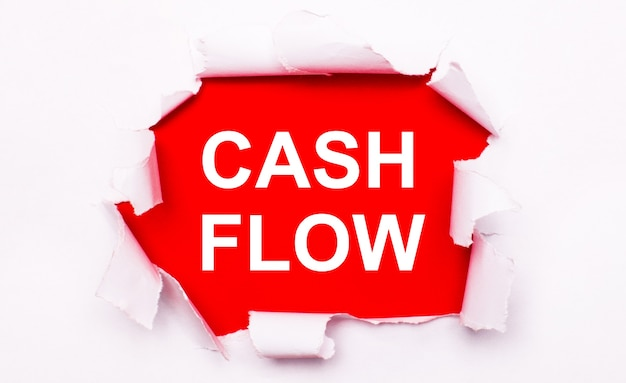 Livro branco rasgado encontra-se sobre um fundo vermelho. em vermelho, o texto é branco cash flow