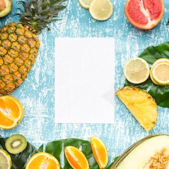 Livro branco rodeado de frutas exóticas