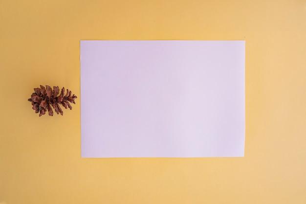 Livro branco sobre fundo de papel de cor pastel amarelo com decoração de flores de abeto. cartão de visitas. cartão de visita, livro branco. mockups de papel