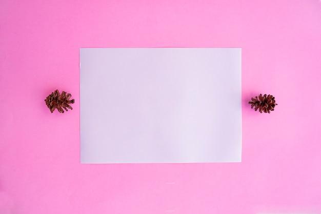Livro branco sobre fundo de papel rosa pastel com decoração de flores de abeto. cartão de visitas. cartão de visita, livro branco. mockups de papel