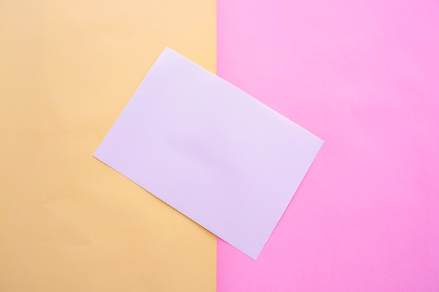 Livro branco sobre um fundo de papel pastel de duas cores rosa e amarelo. cartão de visitas. cartão de visita, livro branco