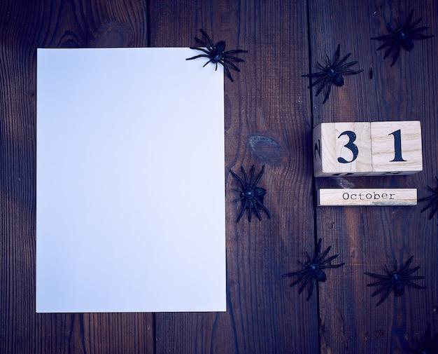 Livro branco vazio, estatuetas de aranha preta e calendário retrô de madeira