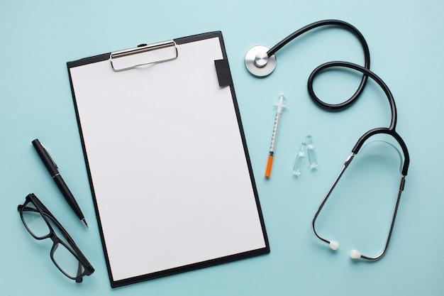 Livro branco vazio na prancheta perto do estetoscópio; injeção; caneta e óculos sobre a mesa azul