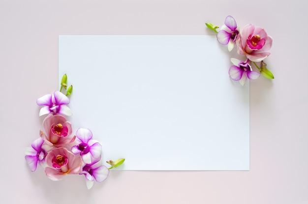Livro branco vazio para texto com flor de orquídeas de dois coner em fundo rosa pastel.