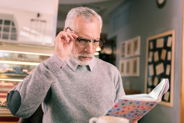 Livro científico. homem barbudo esperto se sentindo um pouco emocionado depois de ler um livro científico polêmico