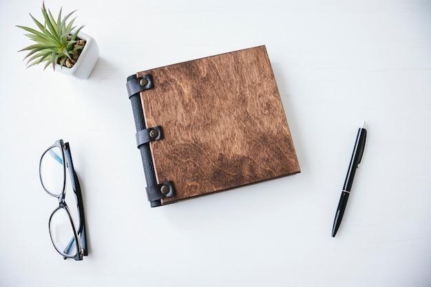 Livro com capa de madeira e caneta