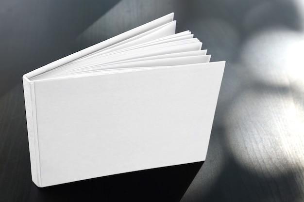 Livro com capa em branco em superfície de madeira escura