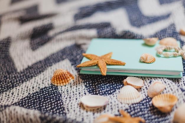 Livro com estrela do mar e conchas