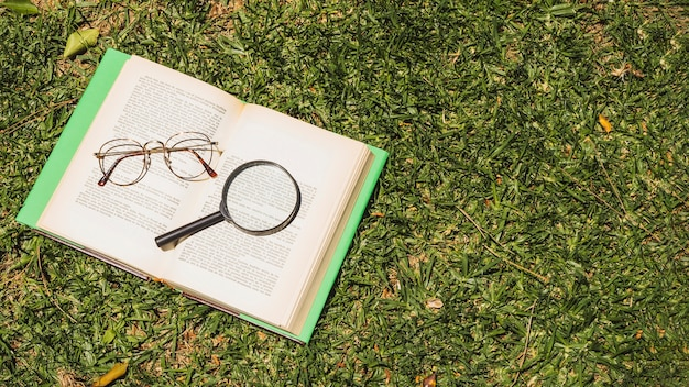 Livro com implementos ópticos na grama verde
