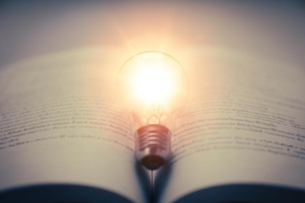 Livro com lâmpada incandescente conhecimento de autoaprendizagem ou educação e conceito de estudo de negócios
