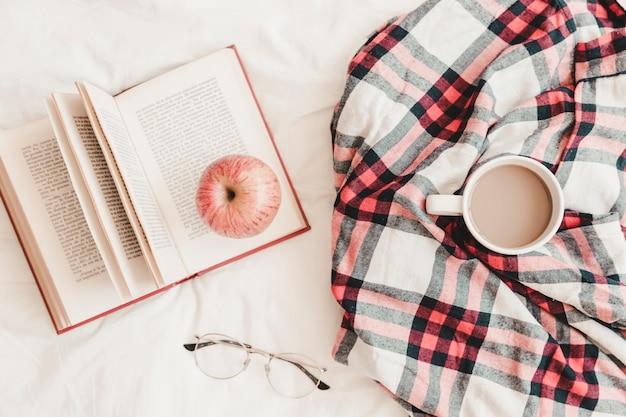 Livro com maçã nele perto de bebida quente em xadrez e óculos