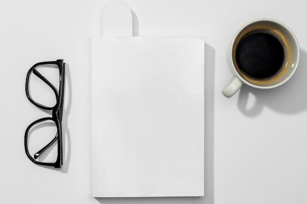 Livro com óculos de leitura e xícara de café