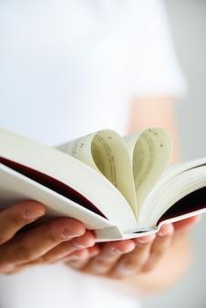 Livro com páginas abertas e forma de coração nas mãos da garota.