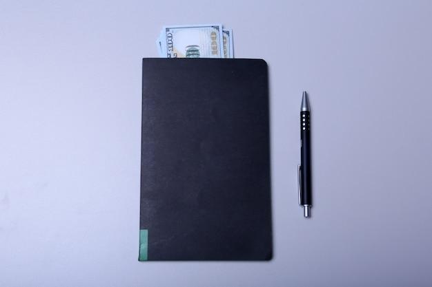 Livro com vista superior de dinheiro e caneta