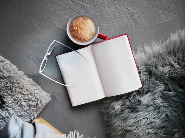 Livro com xícara de café e almofadas ao redor em fundo de textura de cimento