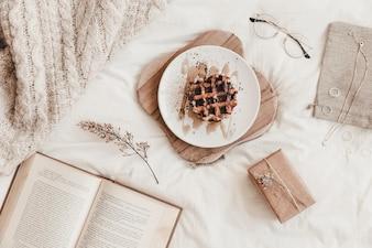 Livro, comida e outras coisas no lençol