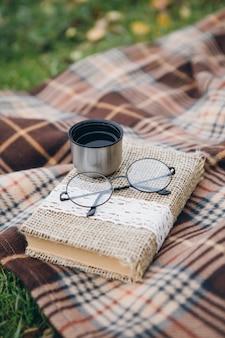 Livro, copos e chá quente de uma garrafa térmica mentem sobre um cobertor