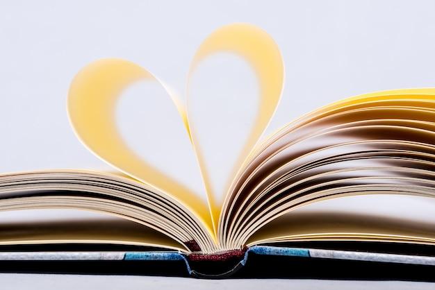 Livro dado forma coração. página do livro na forma do coração, foco no primeiro plano.