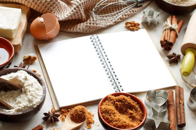 Livro de culinária em branco, ingredientes e utensílios de perto