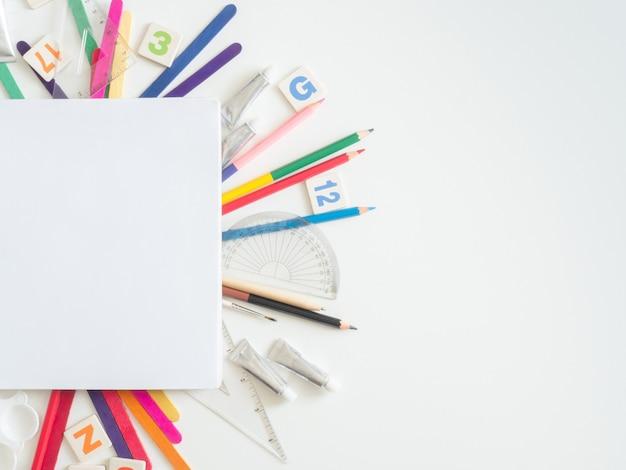Livro de desenho, giz de cera, lápis de cor e papelaria escolar em branco