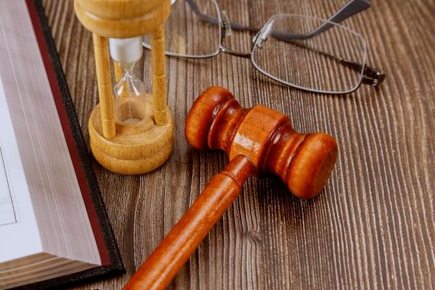 Livro de direito aberto com o martelo de um juiz de madeira na mesa em um tribunal ou escritório de aplicação da lei.