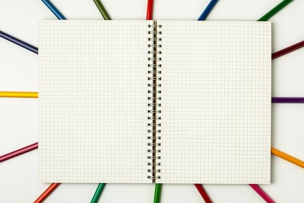 Livro de grade e lápis colorido sobre fundo branco