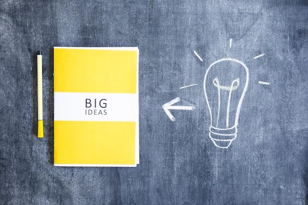 Livro de grandes idéias com caneta de feltro e mão desenhada lâmpada na lousa