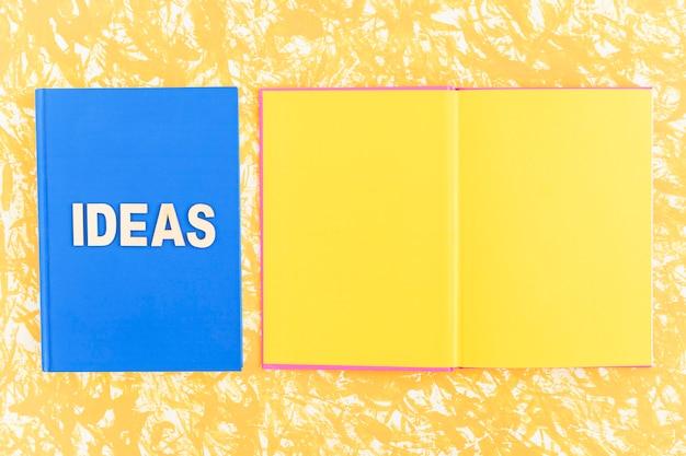 Livro de idéias perto do livro de página amarela aberta no pano de fundo amarelo